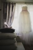Elegant bridal shoes on pillow and wedding dress Royalty Free Stock Photo