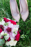 Elegant bridal shoes and wedding bouquet lying on a grass Stock Images