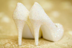 Elegant bridal white shoes with rhinestones, high heels, closeup. Elegant bridal white shoes with rhinestones on beige background, high heels, closeup royalty free stock image
