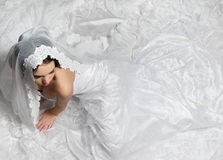 Elegant Bride from Above. Elegant bride sitting on the floor with long white lace wedding dress Stock Image