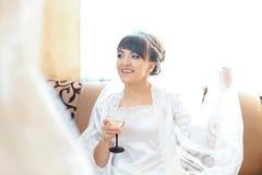 Elegant bride in bathrobe holding wineglass. Wedding, preparation. wedding day morning of the bride stock photography