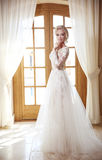 Elegant bride in fashion wedding dress. Blond woman model in white bridal gown with skirt posing in front of curtains window, ind stock photo
