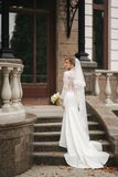 Elegant bride in gorgeous wedding dress stand on the stairs by palace.  stock photos