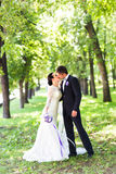 Elegant bride and groom kissing outdoors on a wedding day royalty free stock photo