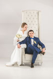 Elegant bride and groom posing on chair at studio Stock Photography