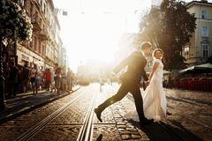 Elegant bride and groom running and smiling in european city str Stock Photo