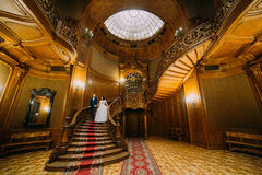 Elegant bride and groom stepping down large wooden stairs, posing in rich interior of old classic mansion Royalty Free Stock Photography