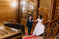 Elegant bride and groom stepping up large wooden stairs, posing in luxurious interior of old classic mansion Stock Photography