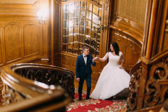 Elegant bride and groom stepping up large wooden stairs, posing in rich interior of old classic mansion Stock Photos