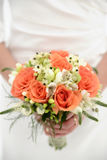 Elegant bride holding a bouquet with mixed flower and orange accents. Beautiful colorful wedding bouquet in the foreground with orange roses and white freesias royalty free stock photography