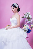 Elegant bride looking away while sitting on chair against pink background Royalty Free Stock Photos
