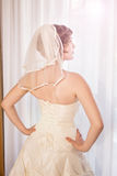 Elegant bride looking out a window Royalty Free Stock Image