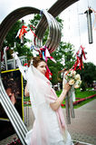 Elegant Bride at metal installation in park Royalty Free Stock Photos