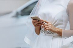 Elegant bride with phone in hands. On a white background royalty free stock photo