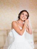 Elegant bride putting on earrings, preparing for wedding Stock Photos