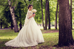 Elegant bride in wedding dress with dipped hem in full length on a background of a forest or Park.  stock photos