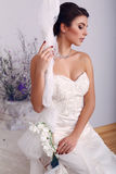 Elegant bride in wedding dress sitting on swing at studio Stock Photo