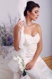 Elegant bride in wedding dress sitting on swing at studio. Fashion photo of beautiful elegant bride in wedding dress sitting on swing at studio stock photo