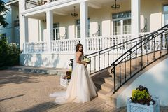 Elegant bride with wedding flowers bouquet, attractive woman in wedding dress. Young girl in a white dress goes the. Stairs of a beautiful white house. Happy Royalty Free Stock Image