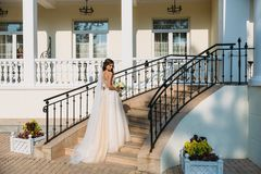 Elegant bride with wedding flowers bouquet, attractive woman in wedding dress. Young girl in a white dress goes the. Stairs of a beautiful white house. Happy Stock Photo