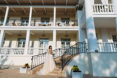 Elegant bride with wedding flowers bouquet, attractive woman in wedding dress. Young girl in a white dress goes the. Stairs of a beautiful white house. Happy Royalty Free Stock Photography