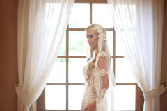 Elegant bride wedding portrait. Fashion white lace veil. Beautiful blond model posing by the window with curtain. Indoor bridal p royalty free stock images