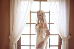 Elegant bride wedding portrait. Fashion white lace veil. Beautiful blond model posing by the window with curtain. Indoor bridal p royalty free stock photography