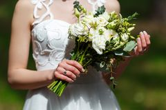 Elegant bride in a white wedding dress with lace holding in hand. S delicate,  trendy bridal bouquet of flowers in white and green colors Stock Photos