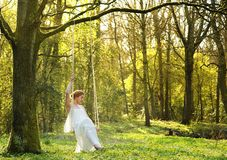 Elegant bride in white wedding dress sitting alone on swing outdoors Royalty Free Stock Photo