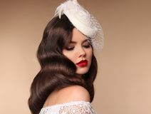 Elegant bride woman portrait in retro hat. Retro lady with wavy. Hairstyle and red lips makeup. Brunette female isolated beige background Royalty Free Stock Images