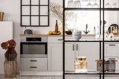 Elegant bright kitchen interior with white cupboards and black shelf.  stock photos