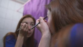 Elegant brown hair girl putting makeup on her face before a mirror in a studio. Cheery view of a young brown hair woman with straight long hair in a dark orange stock video