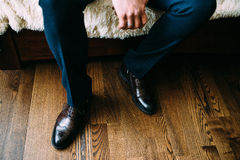 Elegant men's shoes brown worn by the man in blue trousers sitting on the couch. Against the background of the brown floor. Close-up Stock Photo