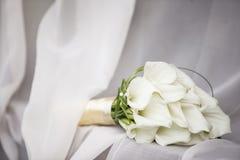 Elegant brud- bukett av vita callaliljor, boutonniere på tabellen arkivbilder