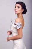 Elegant brud i bröllopsklänning med maskeringen i henne händer Arkivfoton