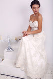 Elegant brud i bröllopsklänningen som poserar i dekorerad studio Royaltyfri Fotografi