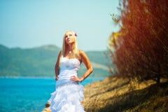 Elegant brud på havet i natur, härlig blondin på solnedgången som tycker om solen arkivbilder