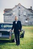 Elegant brudgum i svart dräkt nära bilen arkivfoto