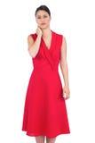 Elegant brunett i den röda klänningen som har huvudvärk Arkivfoto