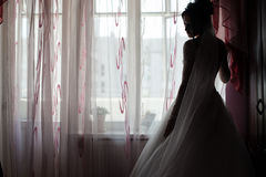 Elegant brunette caucasian bride posing near window before the w Royalty Free Stock Photography