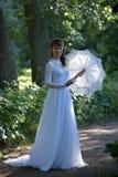 Elegant brunette in een uitstekende witte kleding stock foto's