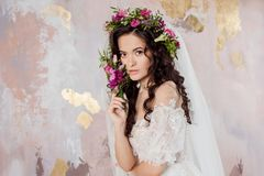 Elegant brunette girl bride with flowers. Beautiful young bride in a lush wedding wreath of fresh flowers. Studio portrait stock images