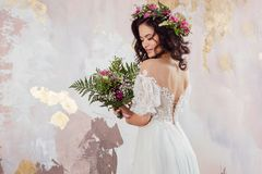 Elegant brunette girl bride with flowers. Beautiful young bride in a lush wedding wreath of fresh flowers. Studio portrait royalty free stock photo
