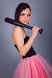 Elegant brunette girl with earrings in pink and black dress with a baseball bat Stock Photography