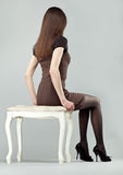 Elegant brunette girl sitting on a chair Stock Photo