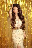 Elegant brunette in golden sparkling dress. Fashion Glamour styl Stock Photo
