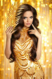 Elegant brunette in golden sparkling dress. Fashion Glamour styl Royalty Free Stock Photos