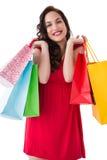 Elegant brunette in red dress holding shopping bags Stock Image