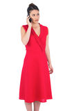 Elegant brunette in red dress on the phone posing Stock Image