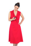 Elegant brunette in red dress sending text message Royalty Free Stock Images